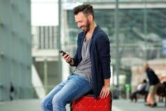Voyageur âgé par milieu de sourire s'asseyant sur la valise Images libres de droits