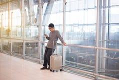 Voyageur asiatique d'homme à l'aide du téléphone portable dans l'aéroport, mode de vie utilisant le concept de connexion de télép Image stock