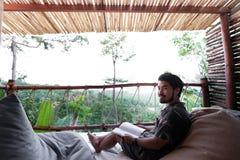 Voyageur asiatique d'hommes utiliser la chemise noire tandis que le livre de lecture regardant ? la cam?ra et se reposant sur le  images stock