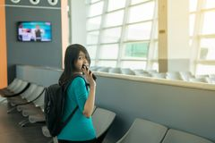 Voyageur asiatique de femme employant l'Internet de téléphone portable et le wifi dans l'aéroport, mode de vie utilisant le conce Photo stock