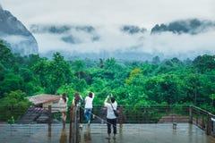 Voyageur asiatique de groupe en pleuvant le jour VangVieng images stock