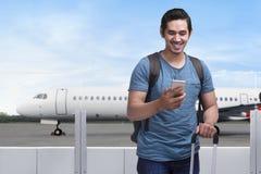 Voyageur asiatique heureux d'homme se tenant avec le sac et le téléphone portable Photos stock