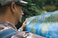 Voyageur avec la cascade se tenante prêt de sac à dos et regards au concept de tourisme de voyage de vacances de carte image libre de droits