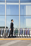 Voyageur avec la valise à côté de la rangée des chariots de bagage à l'aéroport Image stock