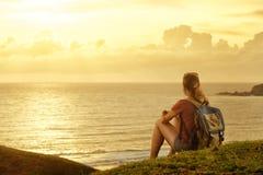 Voyageur avec le sac à dos appréciant le coucher du soleil écoutant la musique sur le pe Photographie stock libre de droits
