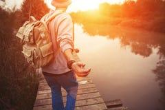 Voyageur avec le sac à dos marchant au-dessus du pont en bois sur le lac Photo libre de droits