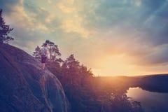 Voyageur avec le sac à dos regardant le coucher du soleil près de la rivière Images stock