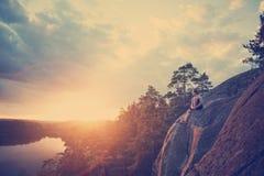 Voyageur avec le sac à dos reposant et regardant le coucher du soleil près de la rivière Photo libre de droits