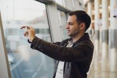 Voyageur avec le téléphone portable à l'aéroport prenant la photo de ses avions Équipements de contrôle du trafic aérien au Photographie stock libre de droits
