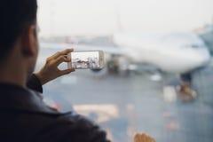 Voyageur avec le téléphone portable à l'aéroport prenant la photo de ses avions Équipements de contrôle du trafic aérien au Images stock