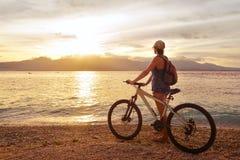 Voyageur avec le vélo appréciant le coucher du soleil sur le fond du photo libre de droits
