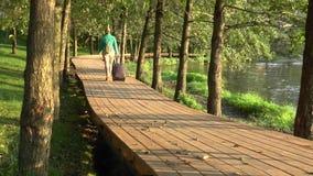 Voyageur avec une valise et un sac à dos marchant sur un sentier piéton en bois par la rivière banque de vidéos