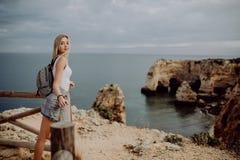 Voyageur blond de femme de jeune beauté regardant la mer et la falaise sur la belle plage du Portugal voyage et concept actif de  images libres de droits