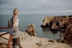 Voyageur blond de femme de jeune beauté regardant la mer et la falaise sur la belle plage du Portugal voyage et concept actif de  photographie stock