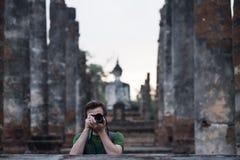 Voyageur caucasien faisant la photo tout en voyageant au temple de bouddhisme en Thaïlande Images stock