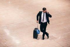 Voyageur d'affaires faisant un appel téléphonique tout en attendant le vol Photographie stock