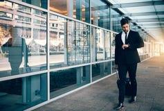 Voyageur d'affaires marchant dans l'aéroport et regardant sa montre Photo stock