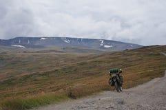 Voyageur d'enduro de moto avec des valises se tenant sur la route rocheuse extrême dans une vallée de montagne Photos libres de droits