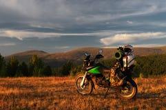 Voyageur d'enduro de moto avec des valises se tenant sur un plateau orange large de pré de montagne d'aube de coucher du soleil Photo stock