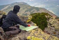 Voyageur d'homme sur le sommet de montagne Regarde la carte avec l'itinéraire image libre de droits
