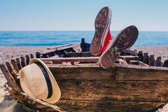 Voyageur dans des chaussures rouges s'étendant dans le vieux bateau et repos Photos stock