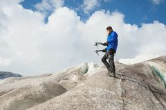 Voyageur dans un chapeau et des lunettes de soleil se tenant avec la hache de glace dans les montagnes neigeuses sur le glacier V image stock