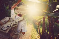 Voyageur de femme avec le sac à dos marchant par des palmiers au coucher du soleil Photo stock
