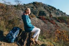 Voyageur de femme détendant sur un tronçon d'arbre sur un fond de roche Photo libre de droits