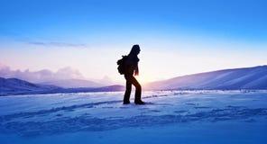 Voyageur de femme trimardant en montagnes de l'hiver Photographie stock