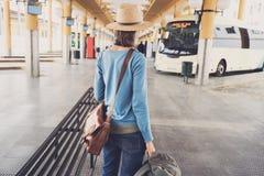 Voyageur de jeune femme attendant un autobus sur une gare routière, un voyage et un concept actif de mode de vie photos stock