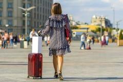 Voyageur de jeune femme portant son sac rouge de chariot sur la rue Photos stock