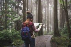 Voyageur de jeune femme regardant la carte et marchant dans l'educa de nature photo stock
