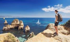 Voyageur de jeune femme regardant la mer dans la ville de Lagos, région d'Algarve, Portugal voyage et concept actif de mode de vi photos libres de droits