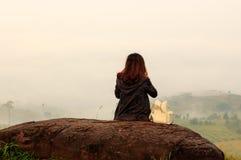 Voyageur de jeune femme s'asseyant sur la montagne et regardant le brouillard dans le matin photo stock