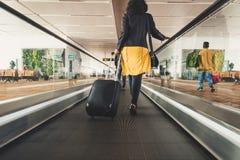 Voyageur de jeune fille marchant avec la valise de transport de prise dans l'a Photographie stock