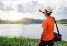 Voyageur de jeune homme avec du temps de coucher du soleil de réservoir et de montagne photographie stock