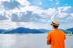 Voyageur de jeune homme avec du temps de coucher du soleil de réservoir et de montagne images stock