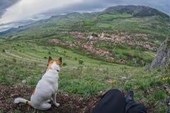 Voyageur et son chien se reposant sur une colline en dehors d'un village Image libre de droits