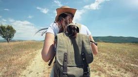 Voyageur européen féminin avec le sac à dos sur la traînée du champ sec au voyage de mode de vie de trekking banque de vidéos