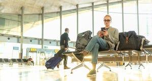Voyageur féminin à l'aide de son téléphone portable tout en attendant pour monter à bord d'un avion aux portes de départ sur le t photographie stock