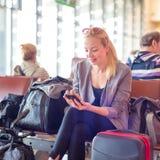 Voyageur féminin à l'aide du téléphone portable tout en attendant sur l'aéroport Images stock