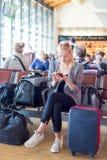 Voyageur féminin à l'aide du téléphone portable tout en attendant sur l'aéroport Photographie stock libre de droits
