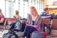 Voyageur féminin à l'aide du téléphone portable tout en attendant sur l'aéroport Photo stock