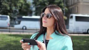 Voyageur féminin élégant adorable à l'aide du smartphone regardant sur la carte électronique au fond de ville banque de vidéos