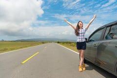 Voyageur féminin arrêtant la voiture sur le bord de la route d'asphalte Photos stock