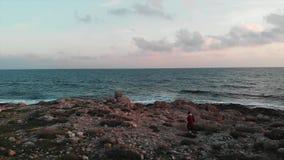 Voyageur féminin caucasien attirant dans la chemise rouge craquant par le bord de la mer rocheux à la plage d'océan au coucher du banque de vidéos