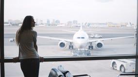 Voyageur féminin caucasien marchant à la fenêtre terminale de salon d'aéroport, mettant le sac vers le bas et regardant la montre banque de vidéos