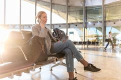 Voyageur féminin parlant à son téléphone portable tout en attendant pour monter à bord d'un avion aux portes de départ sur le ter photos libres de droits