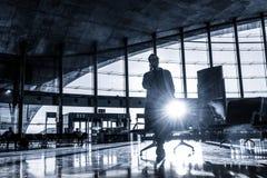 Voyageur féminin parlant à son téléphone portable tout en attendant pour monter à bord d'un avion aux portes de départ sur le ter images stock