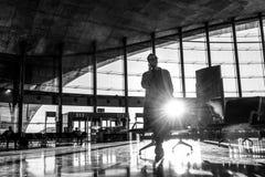 Voyageur féminin parlant à son téléphone portable tout en attendant pour monter à bord d'un avion aux portes de départ sur le ter photographie stock libre de droits